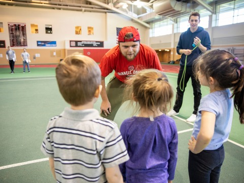 Coaching student talks to three young athletes