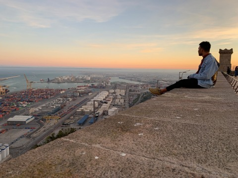 Max Hill sitting on a wall at Castle Montjuic, Barcelona, Spain, at sundown