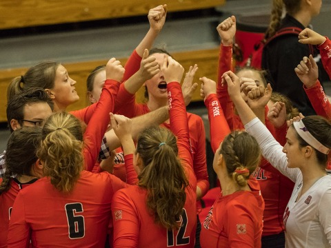 Women's volleyball team huddles together