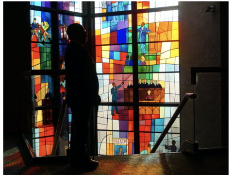 A silhouetted figure in front of stained glass