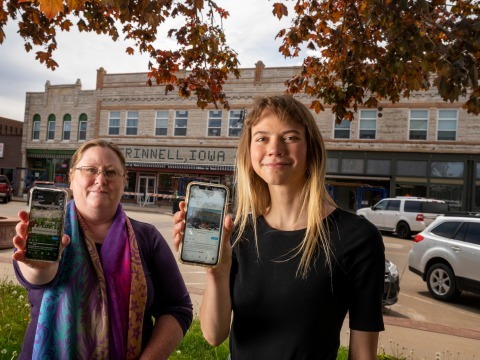 Monique McLay Shore '90 and Allison Cottrell '21 in downtown Grinnell holding up their smart phones