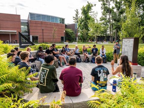 Students have class outdoors near blackboard outside HSSC