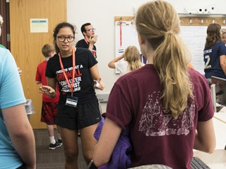 Code camp counselors talk with small groups of campers