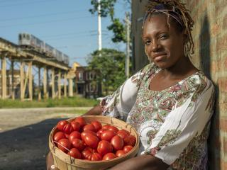 LaDonna Redmond in urban neighborhood carrying basket of tomatoes