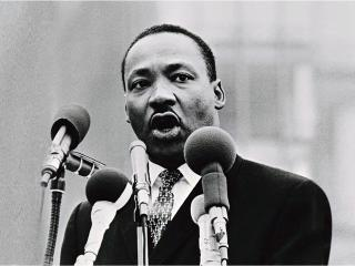 Martin Luther King, Jr. speaking behind several microphones
