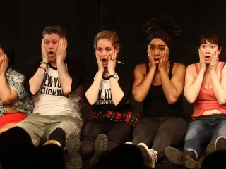 Neofuturists sitting on the floor in a row with surprised expressions