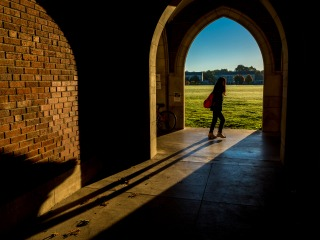 Student passing arches in Gates Rawson Tower