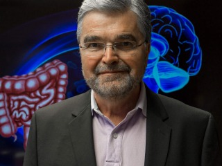Dr. Emeral Mayer stands in front of an illustration of intestines and brain