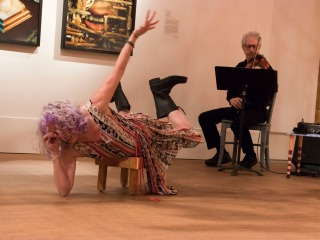 Celeste Miller poses lying crosswise on a stool with violinist behind her