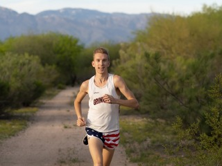 Adam Dalton '16 running on a remote road in the mountains wearing Grinnell shirt