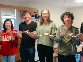 Students holding a long noodle stretched across their hands