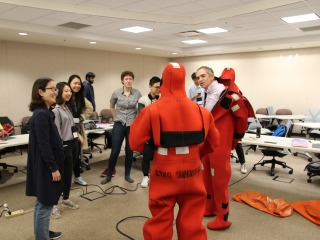 Mark Zimmermann puts on a wetsuit for students during their tour of the Alaska Fisheries Science Center in Seattle