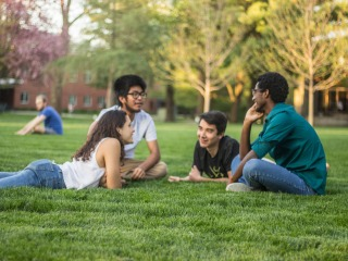 4 students face each other in a circle as they sit or lie on the grass