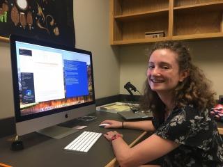 Lauren Frankel in front of computer monitor looking at camera.