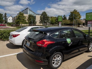 Two zipcars parked in lot across from Chrystal Center