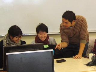 An instructor points to student work on a computer screen while two students look on.