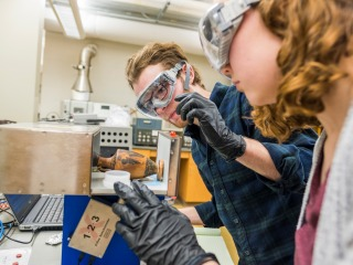 Nora and Ben place a greek vase in a spectrometer machine