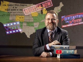 Doug Hess in front of United States map depicting states he has worked with