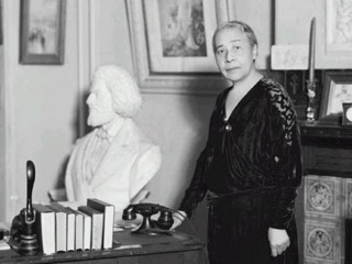 Anna Julia Cooper in a parlor with a bust of Frederick Douglass
