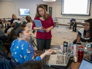Professor Tammy Nyden (center) listens to two students during class