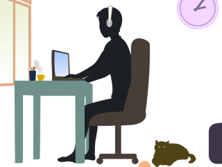 Student sitting at desk w/cat on floor