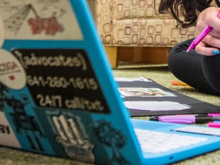 Close-up of a student sitting on the floor with an open laptop
