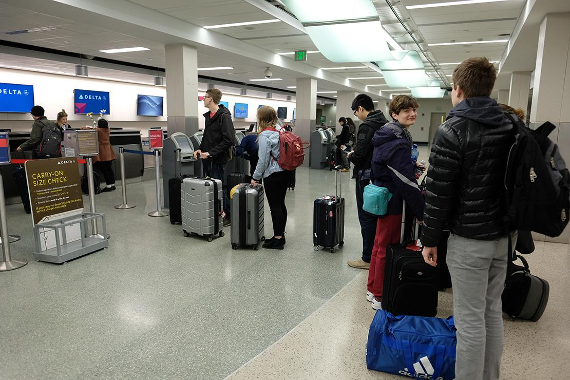 Students with their luggage wait in line to check in at Delta counter