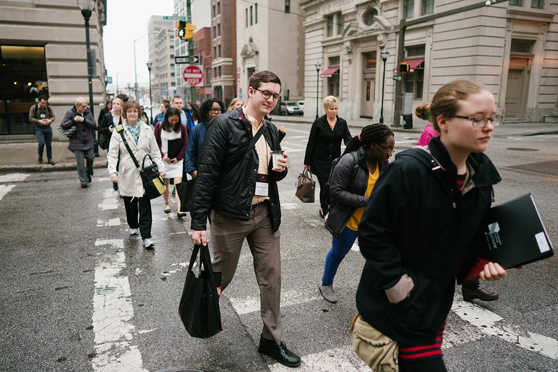 Students and staff with coffee, bags, and Grinnell College lanyards crossing the street