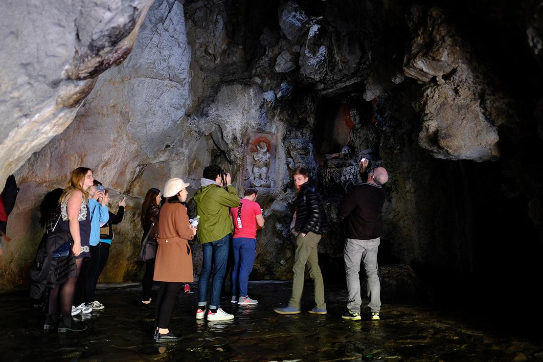 Group looking at small figure carved into a niche in a grotto wall