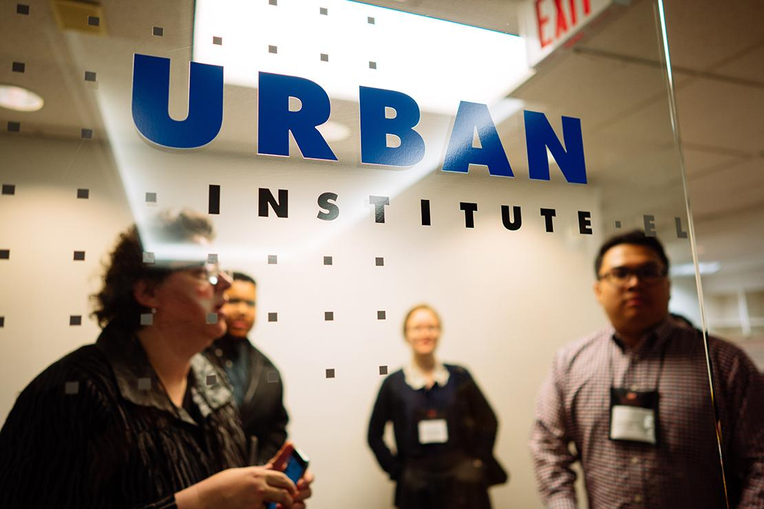 Sarah Purcell and others stand behind a glass wall with Urban Institute logo