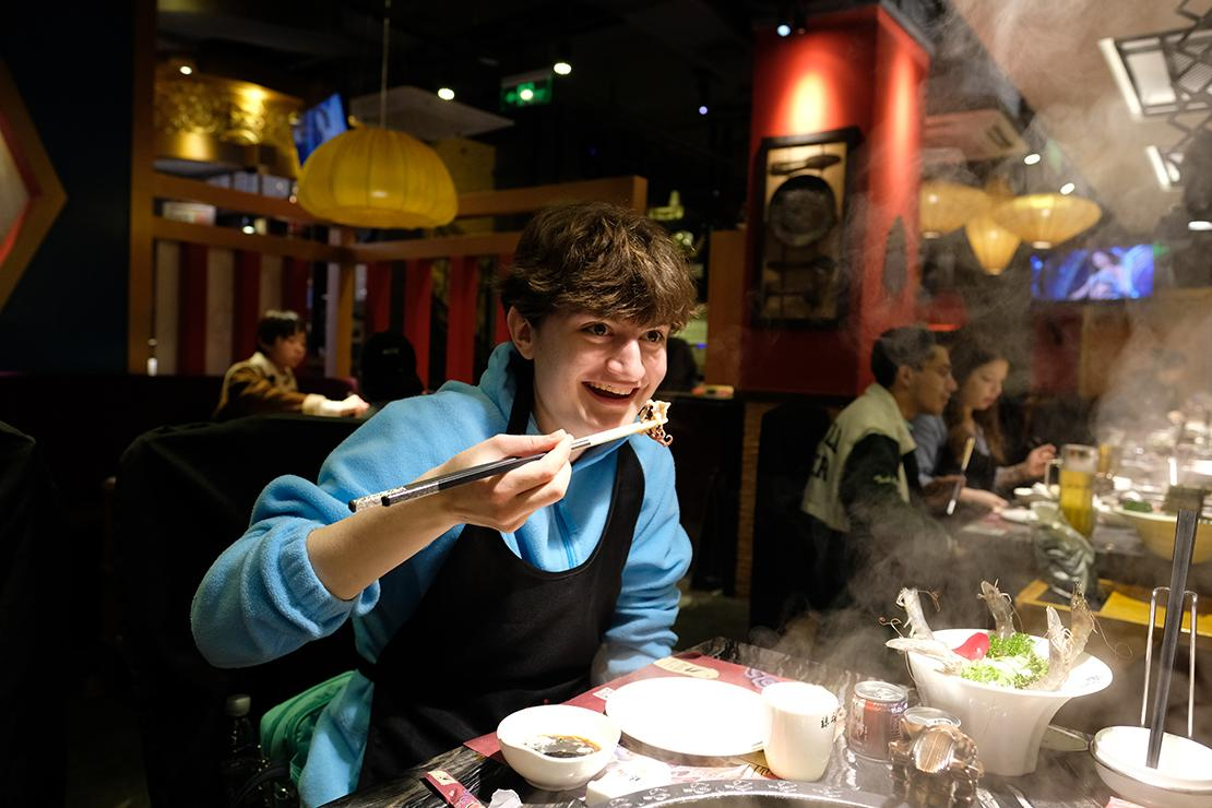 Diner holds small octopus over table wreathed in steam