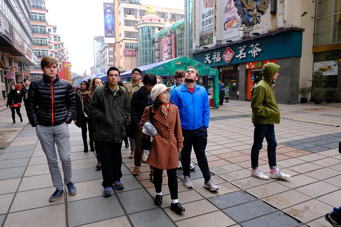 Group walking between buildings at a paved pedestrian area