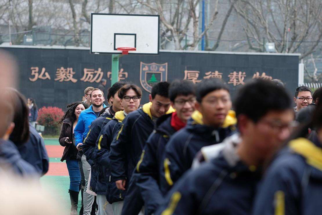 Grinnellians' varied coats stand out from behind a line of Chinese runners dressed in black and yellow coats.