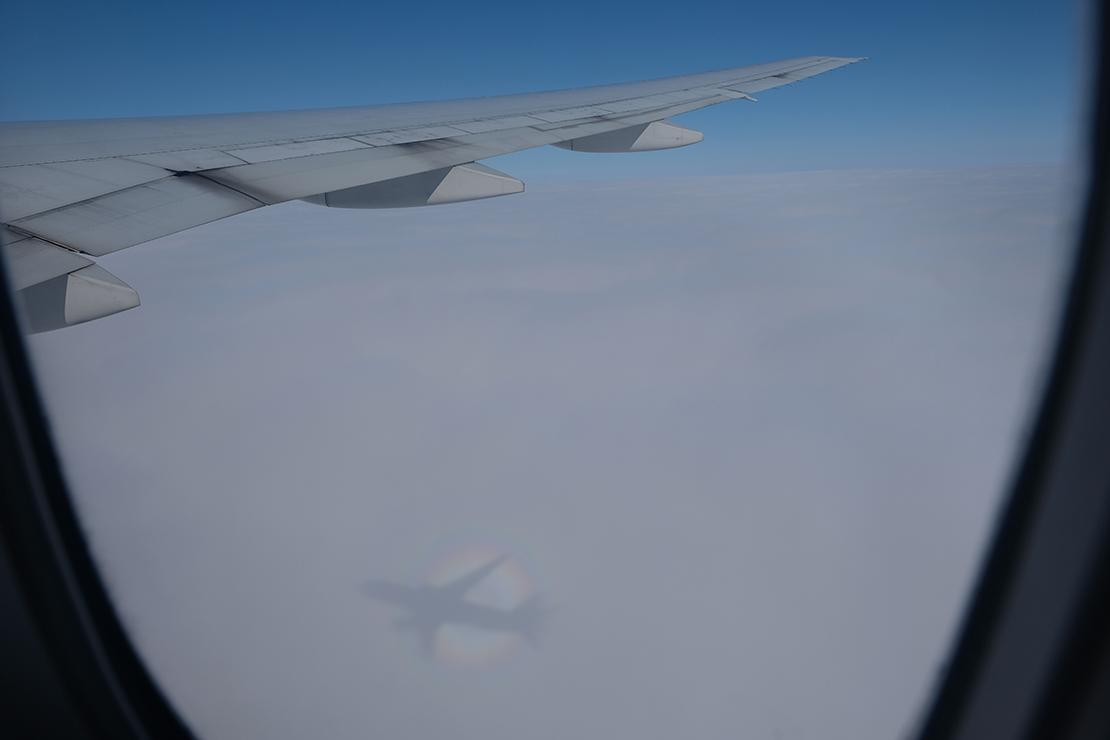 View out of the plan window catches the wing and a shadow of the plane on the clouds below.