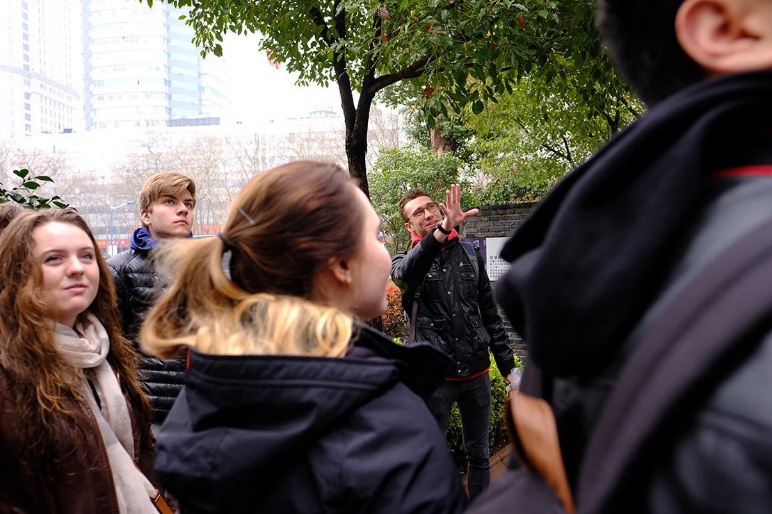 Group, backs to trees, gaze to where Sadkowski is pointing.