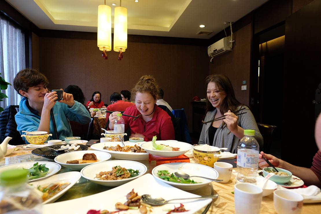Two diners laughing while lifting eels with chopsticks. Table loaded with a variety of food.