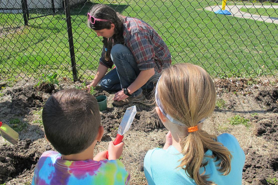 Two children with simple garden tools watch CERA Manager Elizabeth Hill put prairie plants in the ground near the preschool fence.