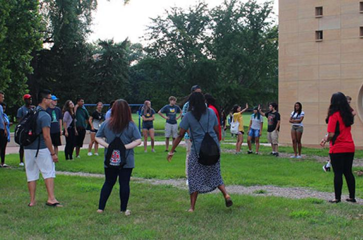 Students and staff stand outside in a large circle doing a group activity.