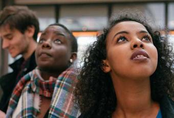 Woman looks intently at something above her head.