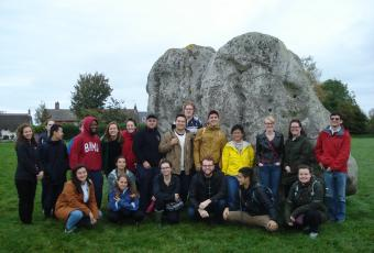 Photo of students that are taking part of the Grinnell-in-London at one of the largest of the stones at Avebury.
