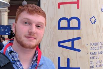 Sage stands in front of Fab Lab conference sign