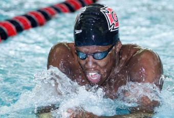 Joshua Tibatemwa '19 swimming in Grinnell's natatorium