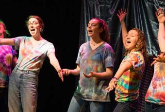 Neverland players in brightly colored tie-dyed shirts and blue jeans enthusiastically performing