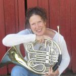 Guinevere McIntyre with her horn in front of a red barn