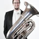 Bo Atlas in a tuxedo posing with a tuba