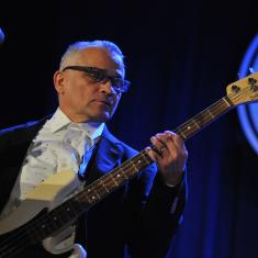 Gabriel Espinosa playing bass on stage with blue backlighting