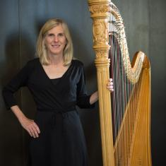 Kristin Maahs standing with her harp against a black background