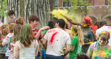 Students covered in Holi colors crowded near tree on Mac Field.