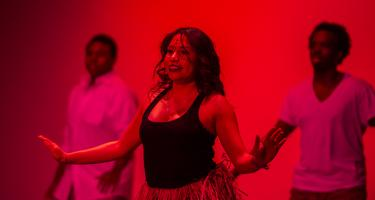 Three performers in red light, focus on woman in front