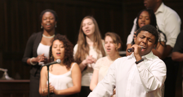 Man singing into a microphone with choir singing behind him